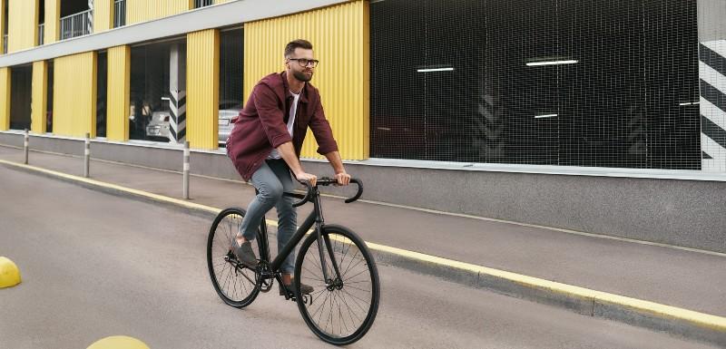 Homme habillé d'un jean et une d'une chemise à carreau qui fait du vélo