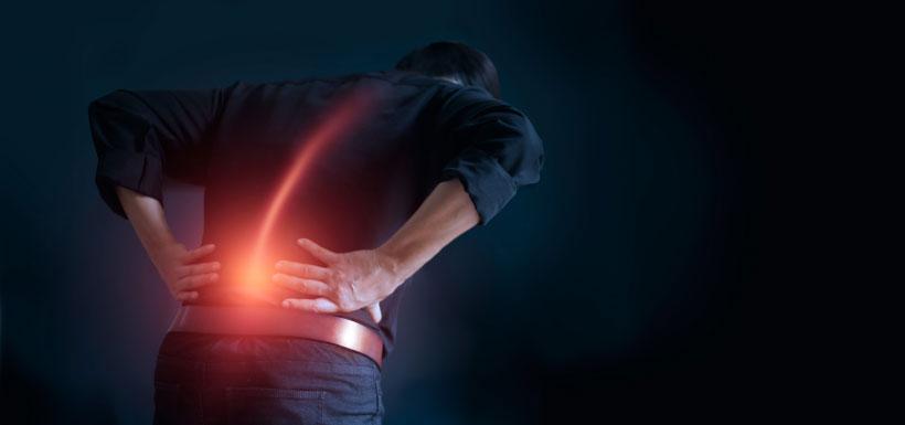 Homme se tenant le bas du dos - les signes à surveiller